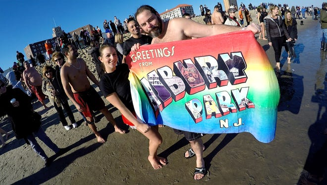 Polar Bear plungers hold an Asbury Park towell after exiting the surf just north of Convention Hall in Asbury Park Sunday January 1, 2017.  The plunge benefits the Shore House and Stephy's Place and is sponsored by the Sons of Ireland.Org.