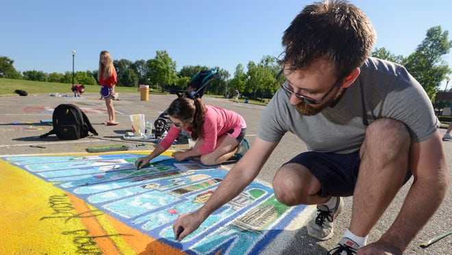 """Ben and Evelyn Shoults work on their entry in the chalk art competition at the 2015 Flimp Festival at the Montgomery Museum of Fine Arts in Montgomery. This year's theme is """"Quilting in the MMFA."""""""