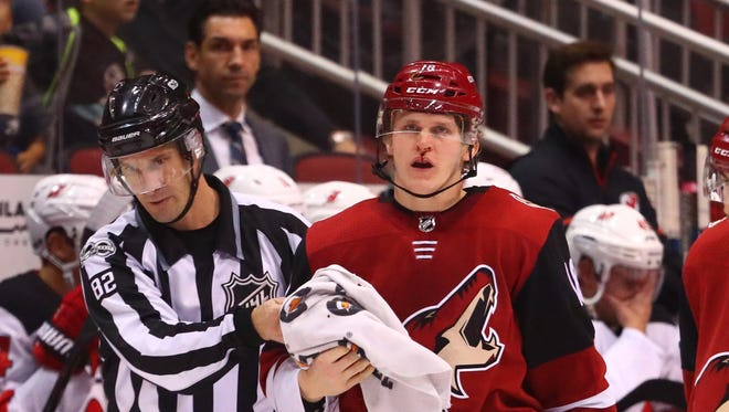 Arizona Coyotes left wing Christian Dvorak (right) is tended to by a referee as he bleeds from an injury in the third period against the New Jersey Devils at Gila River Arena.