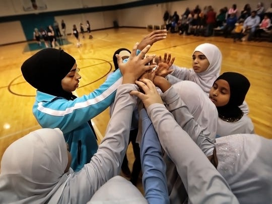 "Bilqis ""Qisi"" Abdul-Qaadir (left), athletic director at Pleasant View School and former Lady Tigers basketball player, gets her girls basketball team together for a cheer before they play a game against the Germantown Grizzlies at Independent Presbyterian Church."