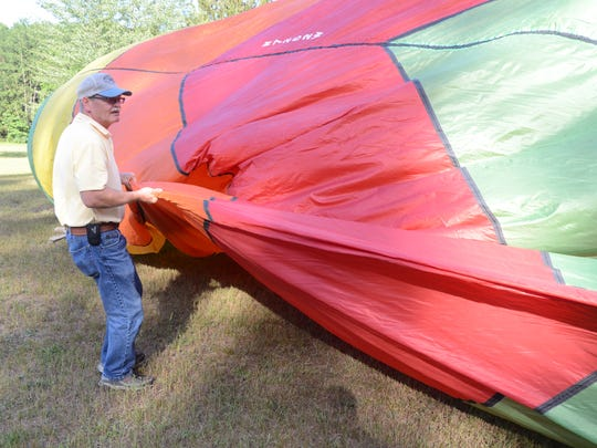 Dale Wilson of Augusta spreads his envelope as he prepares to fly last week.