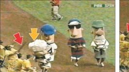 In this video screen grab, Pittsburgh Pirates first baseman Randall Simon (marked by red arrow) can be seen taking a swing at Guido, the Italian sausage character (yellow arrow), during the sausage race at Miller Park on July 9, 2003.