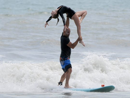 Ed and Kymmie Martinez perform a tandem surfing lift during the Easter Surfing Festival at Lori Wilson Park.