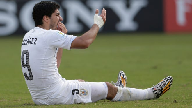 Uruguay's Luis Suarez holds his teeth after running into Italy's Giorgio Chiellini's shoulder during the group D World Cup soccer match between Italy and Uruguay at the Arena das Dunas in Natal, Brazil, Tuesday, June 24, 2014.