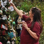 Kathryn Asken hangs an ornament on the butterfly tree in the Alexandria Zoo for her mother.
