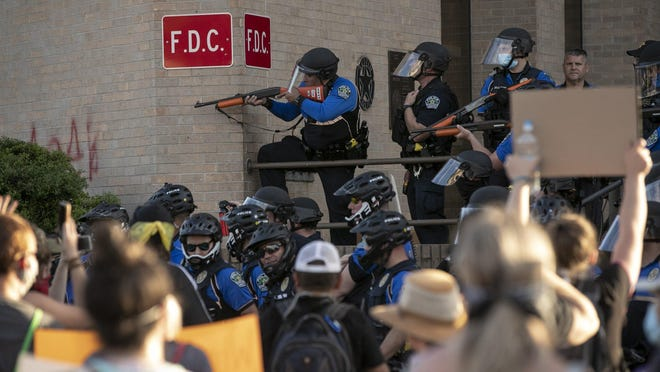 Police and protesters clash Saturday at the Austin Police Department Headquarters during a protest over the death of George Floyd while in custody of the Minneapolis police. Some protesters threw water bottles at the police, and officers responded with pepper spray and less-lethal rounds.