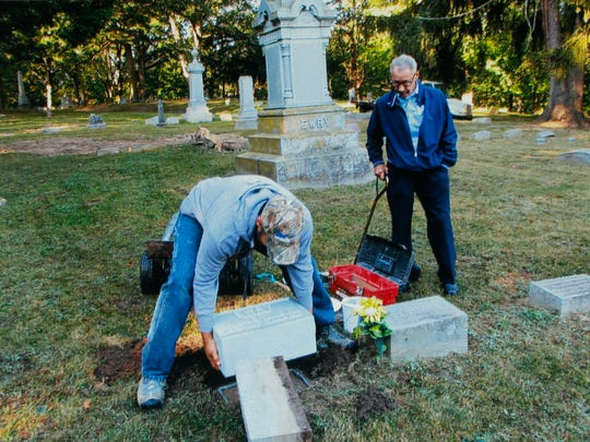Dick Leill, right, watches as a new headstone for Ray