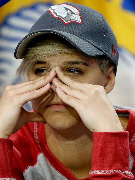 An Arizona Cardinals fan watches during the second half of NFL football game against the Los Angeles Rams, Sunday, Oct. 2, 2016, in Glendale, Ariz. The Rams won 17-13. (AP Photo/Ross D. Franklin)