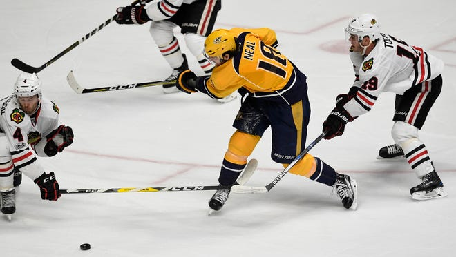 Nashville Predators ring wing James Neal (18) moves the puck surrounded by defenseman Niklas Hjalmarsson (4), defenseman Duncan Keith (2) and center Jonathan Toews (19) during the first overtime of game three in the first-round NHL playoff series at the Bridgestone Arena, Monday, April 17, 2017, in Nashville, Tenn.