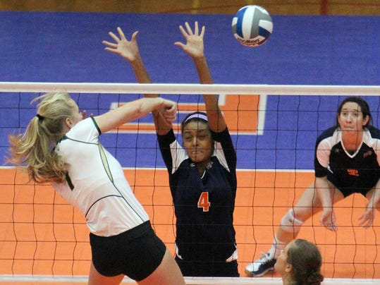 Jamie Colaizzi, 1, of Colorado State goes for a kill as UTEP's Dominique Millette, 4, rises to defend in Memorial Gym.