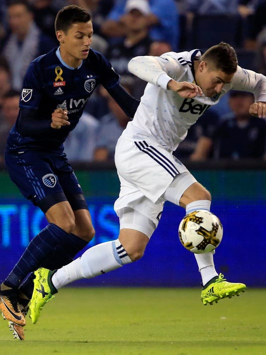 Vancouver Whitecaps defender Jake Nerwinski, right, gets away from Sporting Kansas City forward Daniel Salloi, left, during the first half of an MLS soccer match in Kansas City, Kan., Saturday, Sept. 30, 2017. (AP Photo/Orlin Wagner)