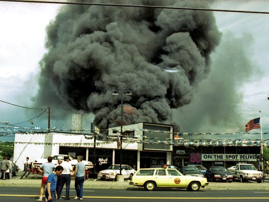 Black smoke billows from the roof of a Ford dealership, which caught fire in Hackensack on July 1, 1988. Five firefighters lost their lives in the inferno.