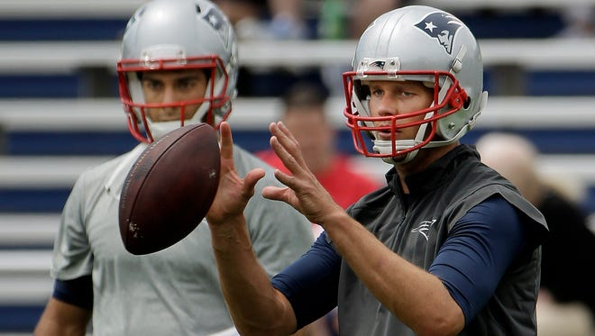 New England Patriots quarterback Tom Brady takes a snap as backup  quarterback Jimmy Garoppolo looks on during an NFL football minicamp Wednesday, June 17, 2015, in Foxborough, Mass.