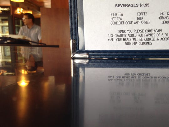 A menu at the Farmers Market restaurant states the eatery's gratuity policy Tuesday.