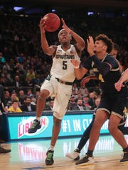 Michigan State guard Cassius Winston scores against Michigan forward Isaiah Livers during the first half of the Big Ten tournament semifinal on Saturday, March 3, 2018,  at Madison Square Garden.