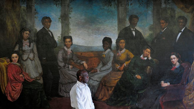 Dr. Paul Kwami, musical director for the Fisk Jubilee Singers, stands in front of a painting of the group that was commissioned by Queen Victoria of England in the 1870s. On Saturday the group will perform in Birmingham, England.