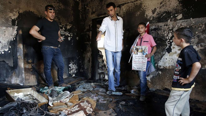 Palestinians look at the damage as they stand in a house set on fire on July 31, 2015, in the West Bank village of Duma.