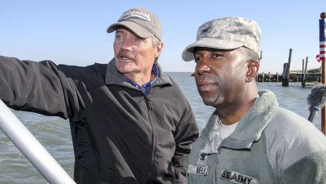"""James """"Ooker"""" Eskridge (left), mayor of the town of Tangier, gives Col. Jason Kelly, commander of the Norfolk District, a boat tour around Tangier Island, on December 4. Kelly came to brief the town of a little more than 700 people on the status of district projects around their island."""