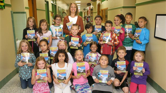 "Third-graders at Glenwood Elementary School in Greenfield hold complimentary copies of the new book ""Fly Guy Presents: The White House"" on Thursday. Author Tedd Arnold has dedicated the book to the kids, who inspired it when they were in the first-grade class of teacher Beth Kaminski (rear center)."
