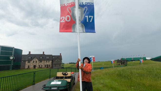 Course worker Jerry Smith erects a U.S. Open banner after strong storms passed through the area Tuesday at Erin Hills in Erin, Wis. Smith said it was the fifth time he has put the banners back up.