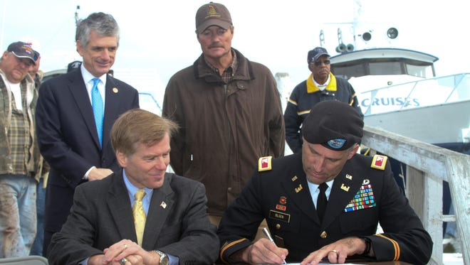 """From left, Congressman Scott Rigell, Gov. Bob McDonnell and Tangier's mayor, James """"Ooker"""" Eskridge, look on as Col. Paul Olsen, Norfolk District commander, signs a proclamation Nov. 20, 2012. The governor and the U.S. Army Corps of Engineers recently announced plans to build a long-awaited jetty to protect the island's endangered harbor. With the Corps' agreement several weeks ago to commit federal funds, a cost-sharing agreement with the Commonwealth was signed and the project approved for study, design and construction."""