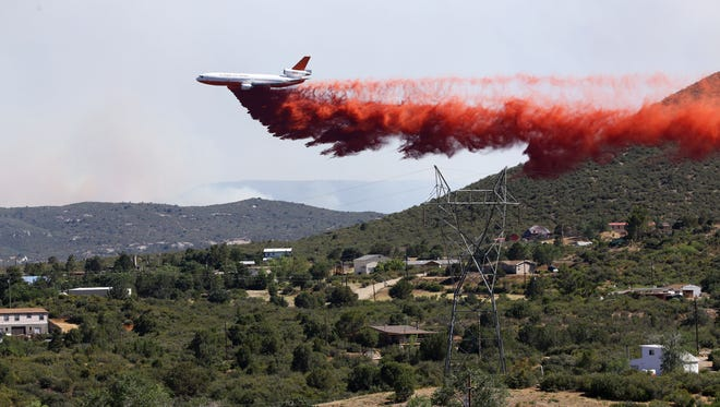 An aircraft drops slurry on the hillside above the community of Blue Hills at the Goodwin Fire on June 28, 2017, in Mayer.