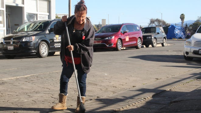 Frances Gonzales sweeps the street after cleaning out her SUV, which she lives out of in Chinatown.