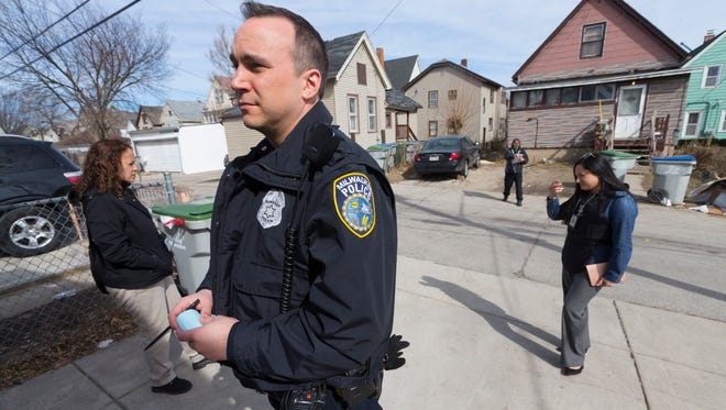 Milwaukee police officer Kevin Vodicka (foreground) and Assistant District Attorney Ann Lopez check on the condition of a boarded-up house Friday following a complaint from neighbors near S. 26th St. and W. Greenfield Ave. in Milwaukee. Since 2000, the Milwaukee County district attorney's office has stationed prosecutors in city neighborhoods. Lopez works in tandem with a police officer and a community organizer. The teams focus on blight and take action designed to improve quality of life, such as shutting down drug houses, holding absentee landlords accountable and making sure taverns follow the rules. At its height, there were seven Community Prosecution Units, one in each police district. Now there are three.