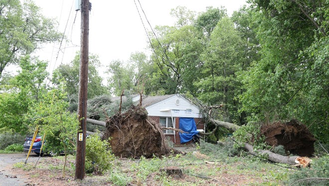 Two trees blown down by Tuesday's storm rest on a home on Rockwell Place in Beacon on May 16, 2018.