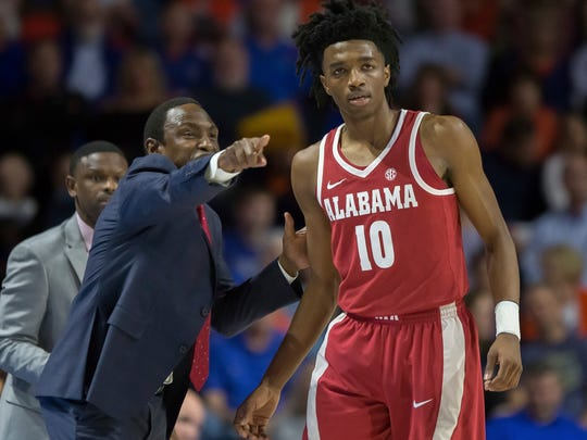 Alabama head coach Avery Johnson, front left, gives instructions to Alabama guard Herbert Jones (10) during the first half of an NCAA college basketball game in Gainesville, Fla., Saturday, Feb. 3, 2018. (AP Photo/Ron Irby)