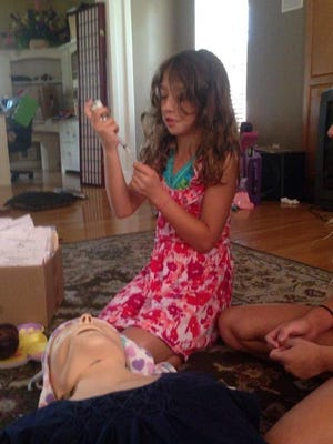 Audrey Stepp, 8, practices administering a life-saving drug to an overdose victim.