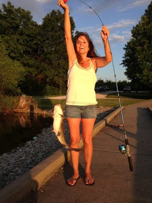 Jamie Lackey with a nice size channel catfish she hooked from a pond.
