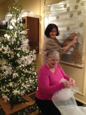 """Mary Lee Minor and Janet Steiner, as Richland County Master Gardeners, spent three days last week decorating the hallway of Kingwood Hall in preparation for holiday visitors. As Janet puts tucks in the mesh fabric, Mary Lee finishes the board with words to the carol """"Silver and Gold."""""""