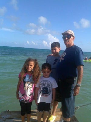 Santo Laboy, of Lajas, Puerto Rico, poses with his grandchildren from Sturgeon Bay: Benjamin Roman, 12, in the rear; Gianna Roman, 9, left, and Andrew Roman, 7, in July 2014.