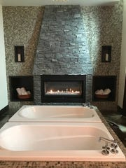 The couple's massage room includes two bath tubs in front of a cozy fireplace at Wind Creek Spa.