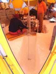 Researchers drill an ice core at their camp on the
