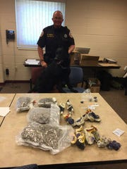 Door County Sheriff Office Deputy Matt Tassoul and his K9 partner, Odinn, pose with the drugs confiscated in arrests June 5, 2018.