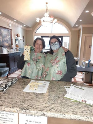 Marian Salwierak and Barbara Kimball with staff wearing the masks and adult bibs they made for the staff and residents at Belfair of Shawnee.