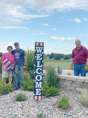 Patty Amiot, Shane Heldstab and Ed Amiot are pictured at the corner of West Sixth Street near Landslide Park.