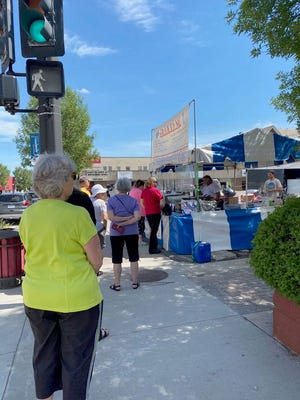 Monday at the corner of Second Street and North Broadway downtown, customers wait in line to order at Greek to Me, out of Warren.
