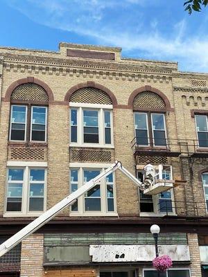 Developer Jeff Evers works on installing window trim on the Fournet Building