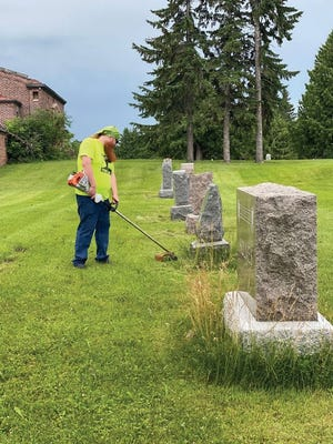 Phillip Shafer cleans up Oakdale Cemetery Saturday