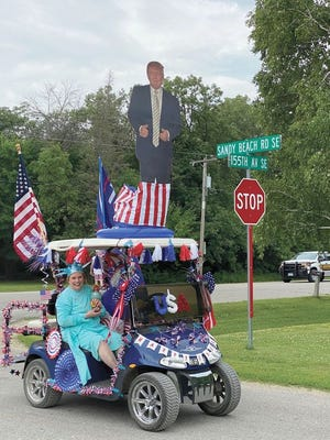 """Shown is a USA-themed golf cart complete with a life-size cutout of President Donald Trump and the """"Statue of Liberty"""" riding shotgun."""