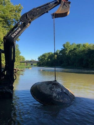 """Delaware workers remove an 880-pound metal disc from the Olentangy River on Aug. 31. The disc -- which turned out to be a floating """"top"""" from a nearby campground -- was discovered during an Aug. 22 river-cleanup event."""