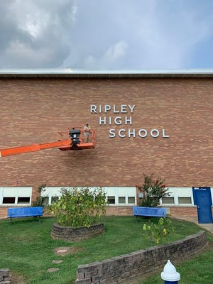 Noel Braley is hoisted up to the roof of the Ripley High School main building to bat proof the facility.