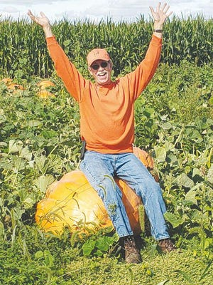 """Pumpkin King Bruce """"O'Lantern"""" Curry sits atop one of the many pumpkins available at Country Corner Farm Market & Pumpkin Patch outside of Alpha."""