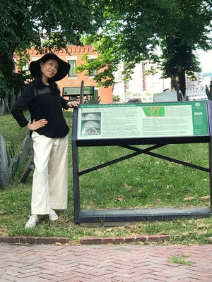 """Dr. Guan Li, a surgeon from Shenzhen, China, checks out the Copp's Hill Burying Ground in the North End. Established in 1659, it was originally named the """"North Burying Ground"""" and was the city's second cemetery. Due to a severe shortage of airline flights back to China thanks to Covid-19, Dr. Guan has been stranded in the U.S. for seven months. While here, she has been writing articles and shooting videos of Boston, including the complete Freedom Trail, for publications in China."""