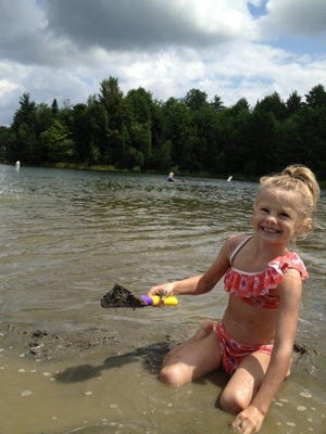 Peyton Peduzzi, 5, of St. Albans, plays on the beach at Waterbury Reservoir this week.
