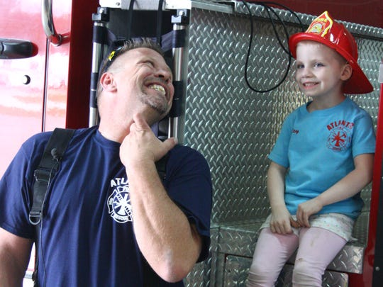 Riley Slauson is shown sitting next to Atlantic Fire Department firefighter Shawn Sarsfield in April 2014 when she was named a firefighter for the day. The fire volunteers and town at the time believed that Riley was dying from cancer. Slauson's mother, Leatha, has since been arrested and accused of faking her daughter's illness to raise money.