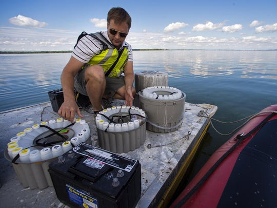 Peter Isles of the University of Vermont's Rubenstein School of Environmental and Natural Sciences collects water samples from a floating automated monitoring station on Missisquoi Bay near Highgate Springs on Wednesday.